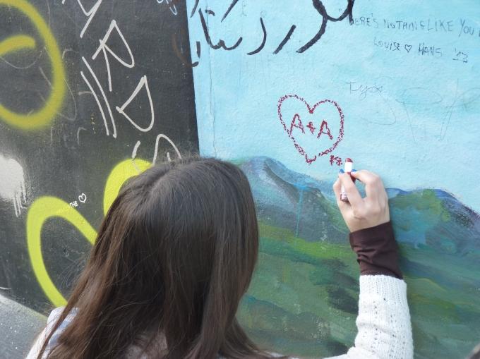 Chica pintando corazones en el cielo del muro (Berlín, 2014)